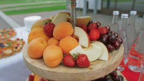 Serving fruits on a stand, peaches, cherries. stock footage