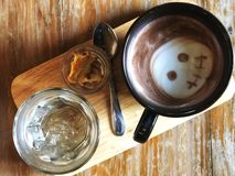 Serving Ghost cute face Latte art in Black cup and water glass on wooden tray and vintage wooden table royalty free stock image
