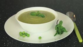 Serving healthy Vegetarian Creme Soup in White Bowl, decorating with mint stock footage