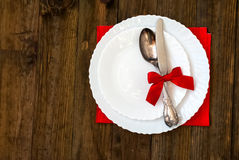 Serving holiday table, spoon, fork, knife, white plates on a woo Royalty Free Stock Photos