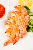 Serving hot shrimps on skewer with sauce Royalty Free Stock Images