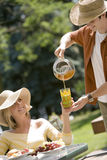 Serving ice tea at picnic. Young man pouring tea for attractive woman at an outdoor picnic lunch royalty free stock photography