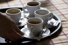 Serving italian coffee. Some cups of italian coffee and a serving hand Stock Photos