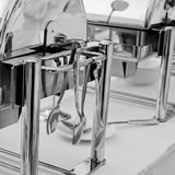 Serving kitchen tongs with chafing dish Stock Images