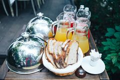 Serving Lid for dishes. dishes under the lid on the buffet table. On the table is bread, a jug of juice, bell stock photo