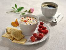 A natural light Breakfast is served on a bright tablecloth. decorated with rose flower. stock photos