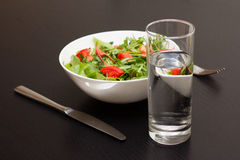 Serving with light salad with tomatoes and a glass of water stock photo
