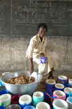 Serving Lunch in Class. March 2, 2007 - A teacher at a rural school in Bolgatanga, Ghana, serves a meal of high energy porridge provided by a humanitarian agency Stock Image