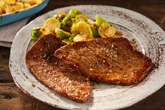Serving of marinated and cooked minute steak with veggies. Serving of marinated and cooked minute steak with sliced brussels sprouts in round ceramic blood stock image