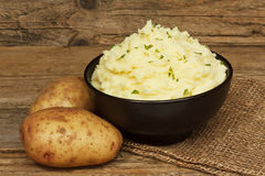 Serving mashed potato. Serving of creamy mashed potato made from boiled potatoes mixed with butter and served in a black bowl on a traditional rustic background stock photo