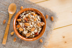 Serving muesli scattering of nuts on wooden table Royalty Free Stock Photo