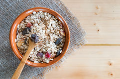 Serving muesli scattering of nuts on wooden table Royalty Free Stock Photos