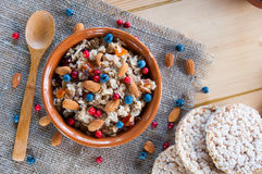 Serving muesli scattering of wild berries, nuts on wooden table Stock Photo