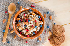 Serving muesli scattering of wild berries, nuts on wooden table Stock Photos