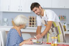 Serving old woman meal. Serving an old women a meal Stock Photos