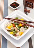 Serving of oriental warm noodle chicken salad. With chopsticks and soy sauce on stripy table cloth Royalty Free Stock Image