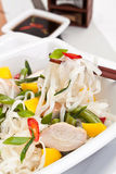 Serving of oriental warm noodle chicken salad. With chopsticks and soysauce Stock Images