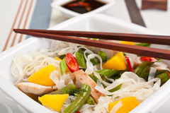 Serving of oriental warm noodle chicken salad. With wooden chopsticks close up Stock Photos