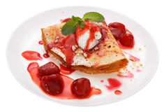 Serving pancakes with ice cream. Nuts and strawberry sauce on the plate Royalty Free Stock Photos