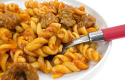 Serving of pasta and sausage on plate with fork Stock Photos