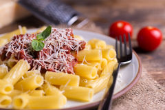 Serving pasta with tomato sauce and parmigiano on natural wooden table. Royalty Free Stock Images