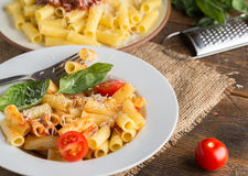 Serving pasta with tomato sauce and parmigiano on natural wooden Stock Image