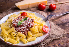 Serving pasta with tomato sauce and parmigiano on natural wooden table. Stock Photography