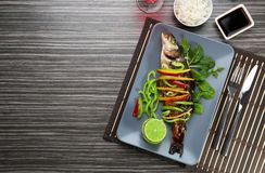Serving plate with delicious fish in sauce and garnish Royalty Free Stock Image
