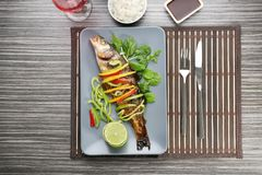 Serving plate with delicious fish in sauce and garnish Royalty Free Stock Images