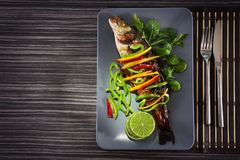 Serving plate with delicious fish in sauce and garnish Stock Image