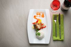 Serving plate with delicious fish, sauce, rice and vegetables Stock Photos