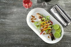 Serving plate with delicious fish in sauce and vegetables Stock Photos