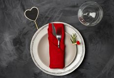 Serving plate for Valentine`s day or romantic dinner at black background. Serving plate for Valentine`s day or romantic dinner with two plates, fork, knife red stock photography