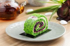 Serving portion of green spinach roll cake with cream cheese and. Currant filling on plate. Restaurant, bakery menu or recipe concept. Copy space royalty free stock photo