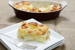 Serving potato Anna. A portion of potatoes anna - layers of wafer-thin potato brushed with butter and baked Royalty Free Stock Image