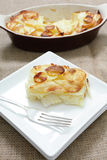 Serving potatoes anna. A portion of potatoes anna - layers of wafer-thin potato brushed with butter and baked - with the serving bowl behind Royalty Free Stock Image