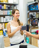 Serving purchaser at cash desk. Smiling young female store clerk serving purchaser at cash desk Stock Photography