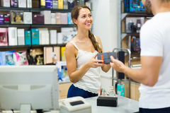 Serving purchaser at cash desk. Young female store clerk serving purchaser at cash desk Stock Photography