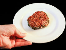Serving raw burger on white plate. Isolated on black Stock Photography