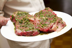 Serving raw steaks. Serve a raw steak with parsley Stock Image