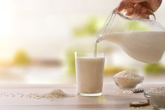 Serving rice drink in a glass in a kitchen Royalty Free Stock Photos