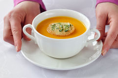Serving roasted-pumpkin soup in a white bowl. Serving homemade roasted-pumpkin soup in white bowl on white tablecloth stock photography