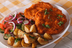 Serving of schnitzel, fried potatoes and salad closeup. horizont. Serving of schnitzel, fried potatoes and vegetable salad on the plate closeup. horizontal Royalty Free Stock Photos