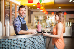 Serving some healthy food to a customer. Attractive young men with a beard serving a salad, some soup and a smoothie on a tray to a customer Royalty Free Stock Photos