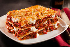 Serving of spicy beef lasagne in a restaurant. Serving of spicy traditional Italian beef lasagne in a restaurant on a modern white square plate with a red napkin royalty free stock photo