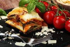 Serving of spicy traditional Italian beef lasagne in a restaurant. Bolognese sauce topped with basil leafs royalty free stock image