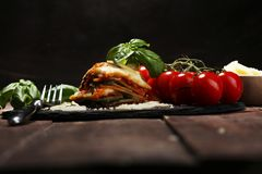 Serving of spicy traditional Italian beef lasagne in a restaurant. Bolognese sauce topped with basil leafs stock photo