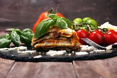 Serving of spicy traditional Italian beef lasagne in a restaurant. Bolognese sauce topped with basil leafs stock image