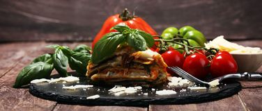 Serving of spicy traditional Italian beef lasagne in a restaurant. Bolognese sauce topped with basil leafs stock photography