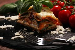 Serving of spicy traditional Italian beef lasagne in a restaurant. Bolognese sauce topped with basil leafs royalty free stock photo